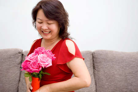 Mother with red roses smiling Stock Photo