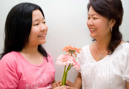 Girl giving gerbera to mum photo