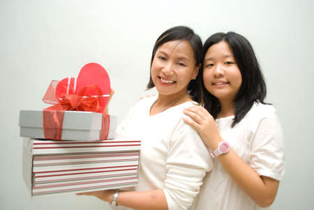 Mother and daughter posing with stack of gifts photo