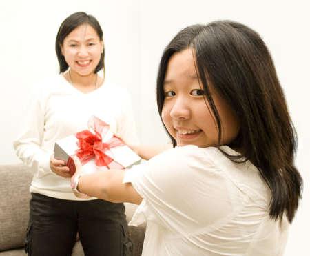 cherishing: girl giving gift to mum