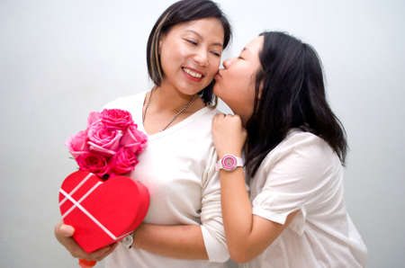 asian girl kissing mum with gifts photo