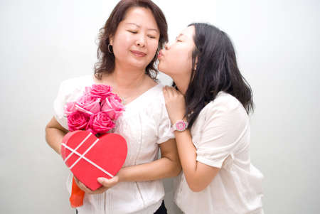 asian girl kissing mum with gifts Stock Photo - 4433805