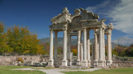 approached: Ancient ruins of Aphrodisias. Tetrapylon gate was the monumental gateway which greeted pilgrims when they approached the Temple of Aphrodite. On the pediment over the west columns were decorated with relief figure of Eros, Archeological park in Turkey. 4k