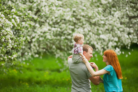 Happy family having fun outdoors in spring garden. Father, mother and child. Family concept photo