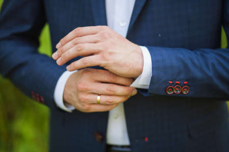 close-up of elegance male hands. man dressed in blue suit and white shirt standing over green nature background. groom in wedding day photo