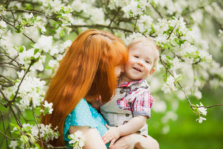 Portrait of happy happy mother and son in spring garden. They playing and laughing. Blooming apple-trees. Family concept. photo