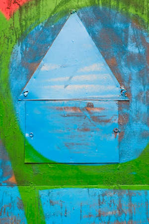 warning notice: blank old warning notice shaped as house. brightly painted in blue and green colors. abstract background. metal texture. nails. notice. announce. warning sign