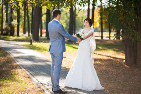 happy bride, groom standing in green park, kissing, smiling, laughing, embracing. lovers in wedding day. happy young couple in love. beautiful healthy people. nature green background photo