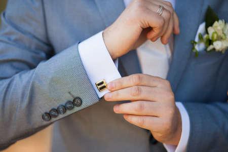 close-up van elegantie mannelijke handen. man gekleed in blauw pak en wit overhemd staande op groene natuur achtergrond. bruidegom in huwelijksdag Stockfoto