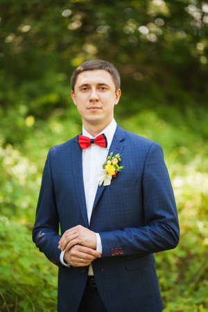 portrait of handsome young man smartly dressed in blue suit, white shirt. groom ready for wedding celebration standing over green nature background and waiting for bride