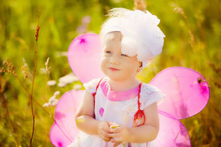 butterfly wings: beautiful carefree girl playing outdoors in field with high green grass. little child picking up wild flowers Stock Photo