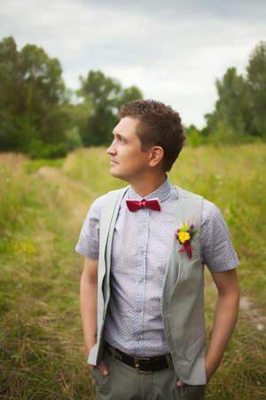 smartly: Portrait of handsome young man smartly dressed. Boutonniere. Red Bowtie. Stylish person