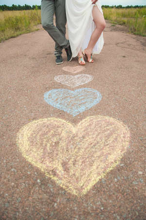 male and female: Heart symbols shaped with crayons on ground and two people in love. Lifestyle and Feelings concept. Romantic woman and man standing outdoors