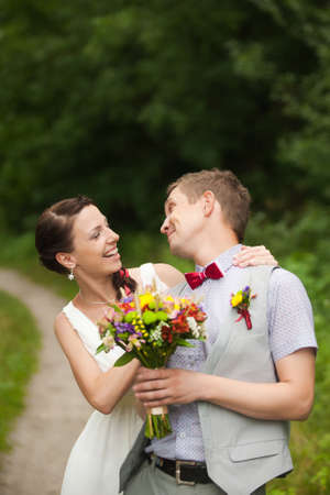 caucasion: happy bride, groom standing in green park, kissing, smiling, laughing, embracing. lovers in wedding day. happy young couple in love.