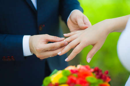 �aucasian: closeup of hands of bridal unrecognizable couple with wedding rings. bride holds wedding bouquet of flowers. exchanging golden rings. love concept. family lifestyle Stock Photo