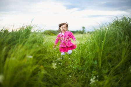 alone: beautiful carefree girl playing outdoors in field with high green grass.freedom concept Stock Photo