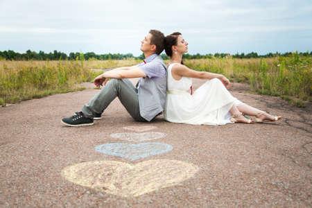 pareja de boda sentado en el suelo. símbolos del amor en pavemant. corazones. personas en el amor. feliz novia y el novio retratos. hombre y una mujer sentados espalda con espalda al aire libre en carretera. los recién casados. día de la boda