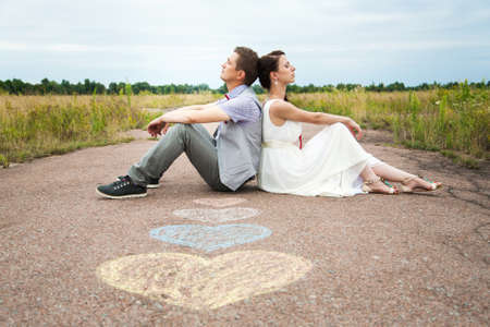 happy young couple: wedding couple sitting on ground. love symbols on pavemant . hearts. people in love. happy bride and groom portraits. man and woman sitting back to back outside on road. newlyweds. wedding day Stock Photo
