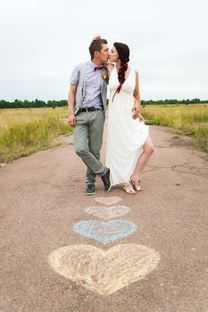 Heart symbols shaped with crayons on ground and two people in love. Lifestyle and Feelings concept. Romantic woman and man standing outdoors