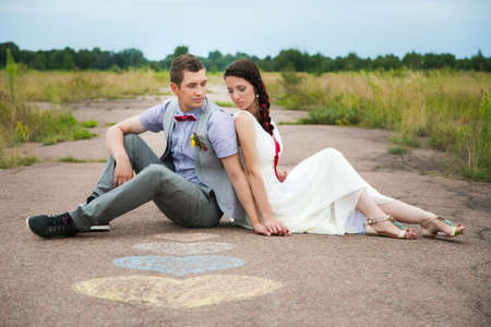 sitting on the ground: wedding couple sitting on ground. love symbols on pavemant . hearts. people in love. happy bride and groom portraits. man and woman sitting back to back outside on road. newlyweds. wedding day Stock Photo