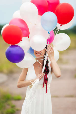 Happy young woman holding in hands colorful latex balloons outdoors. Beautiful bride in white dress having fun in wedding day. Smiling and laughing woman photo
