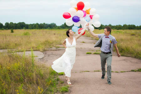 Head and shoulders portrait of happy cheerful couple. Man and woman holding in hands many colorful latex balloons. photo