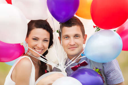Head and shoulders portrait of happy cheerful couple. Man and woman holding in hands many colorful latex balloons. Smiling and looking at camera. photo
