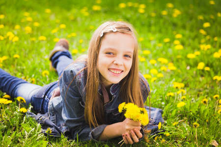spring portrait of smiling girl lying in meadow holding bouquet of dandelions photo