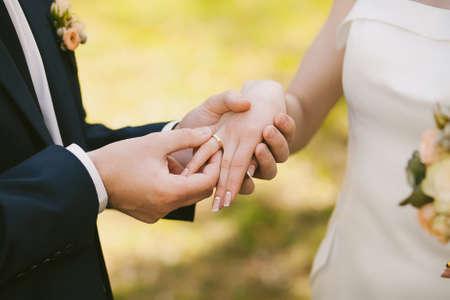 feier: Hochzeitsringe und Hände der Braut und des Bräutigams. Junge Hochzeitspaare an Zeremonie. Ehe. Mann und Frau in der Liebe. zwei glückliche Menschen feiern zu Familie