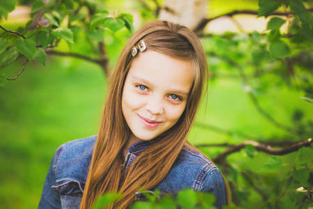 jackets: portrait of pretty teen girl smiling and looking at camera. child in green park. close up of cute 12 years old girl