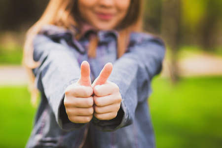 thumb up: Young girl puts her big thumbs up. Portrait of cheerful kid. Smiling girl having fun outside. Happy successful person.