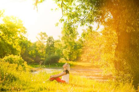 Mujer hermosa que tiene descanso bajo enorme árbol en la puesta del sol afuera. Personas Sunset. Mujer sola disfrutando de la naturaleza del paisaje en la noche. Verano o día de primavera. Chica sentada hierba color imagen horizontal en