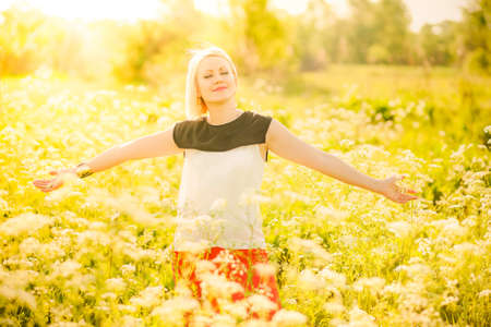 free image: Portrait of beautiful young woman in sunlight. Sunset people. Happy girl enjoying nature in summer meadow full of flowers. Charming free blonde with arms outstretched. Successful person. Success.