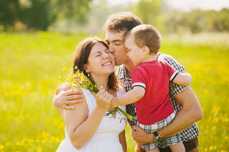 bacio: Famiglia incinta di tre in attesa di bambino. Padre madre e figlio che giocano insieme nella primavera del giorno al di fuori