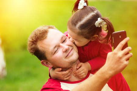 bacio: Ritratto di una bambina baciare suo padre sulla guancia tenendo selfie con il telefono. Chiuda sul fronte di genitore felice con la figlia al di fuori. Archivio Fotografico