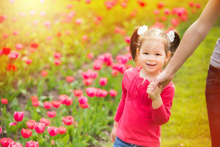 cheerfully: Little girl cheerfully walking in summer urban park holding hand of mother. Mom and child having fun outdoors. Stock Photo