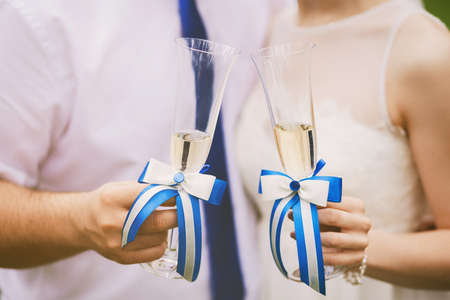 festively: bride and groom holding festively decorated wedding glasses with champagne