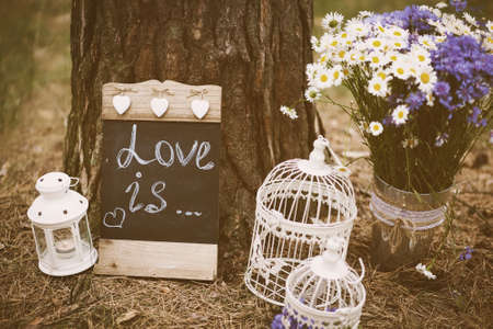 holiday decor: Love is - inscription for wedding. Wedding decor. Image toned in retro style. Stock Photo