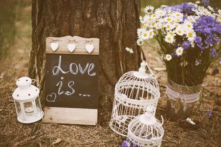 wedding decoration: Love is - inscription for wedding. Wedding decor. Image toned in retro style. Stock Photo