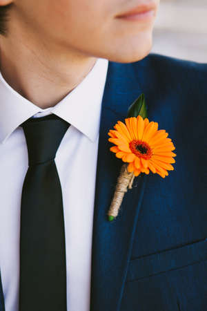 boutonniere: Orange Boutonniere. Groom in the wedding suit.