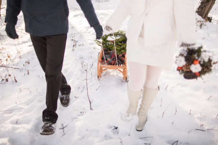 fiesta familiar: Beautiful young wedding couple in love having fun outside on winter snowy day. Groom and bride walking together outside with sleigh. Winter wedding.