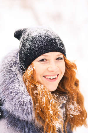 fur trees: Portrait of beautiful young girl dressed in fur coat and black hat at winter snowy trees background. Beauty woman having fun outside in wood on winter snowy day. Happy smiling people in winter time.