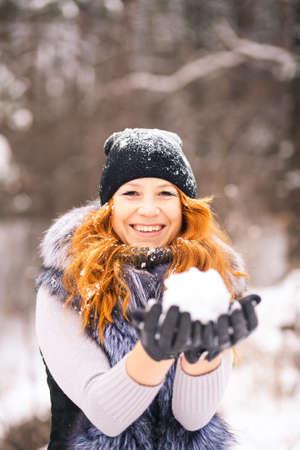 Schönes Mädchen des Winters im Freien Porträt mit Schnee in den Händen. Junge Frau bereit für Schnee auf verschneiten Bäumen Hintergrund weht. Winterspaß. Portrait eines glücklichen Mädchens lächelnd in der Pelzweste, Pullover und Hut gekleidet.