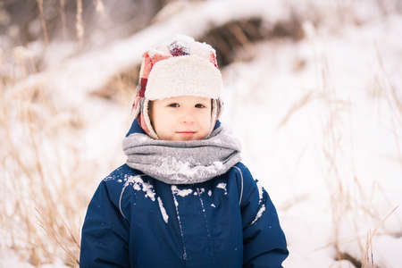 of boy and girl: Portrait of cute little funny child in blue winter thermal upper clothes playing with snow. Active outdoors leisure of children.
