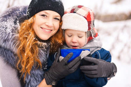 hot day: Baby sitting with young beautiful mother outside at snowy trees winter background and drinking hot tee. Happy family enjoying beautiful winter days on picnic. Stock Photo
