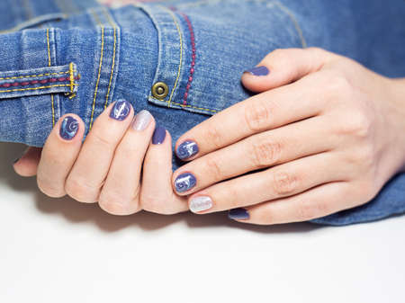 stamping: Close up of female hands with professional blue and silver manicure isolated on jeans clothes texture. Art stamping on nails. Modern gel polish with base coat first and top cure with UV or LED lamp Stock Photo