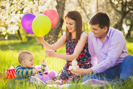 Family on picnic. Dad and mom playing games with little son outside in spring blooming garden. Happy family activity