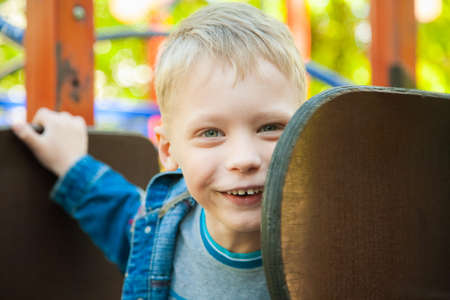 niños rubios: Cerca retrato de la cara divertida niño sonriente. 7 años de edad, jugar al parque infantil. muchacho rubio de raza caucásica vestido con ropa vaquera casuales. Foto de archivo