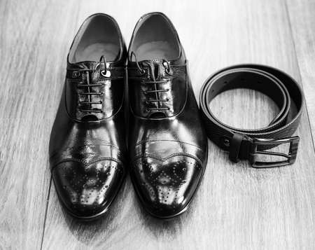 dinner wear: New black man shoes and black belt on wooden brown surface of floor. Black and white picture of male stylish accessories for solemn events Stock Photo