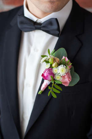 corsage: Close up of  white and pink rose corsage. Beautiful boutonniere pinned on man in black suit, white shirt and black bowtie. Groom or graduate.